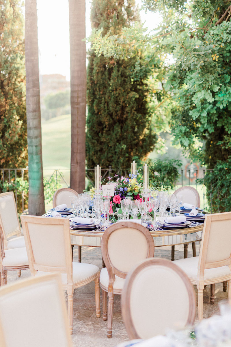 Blue tableware crystal glasses colourful flower arrangements mirror tables wedding Anantara Villa Padierna