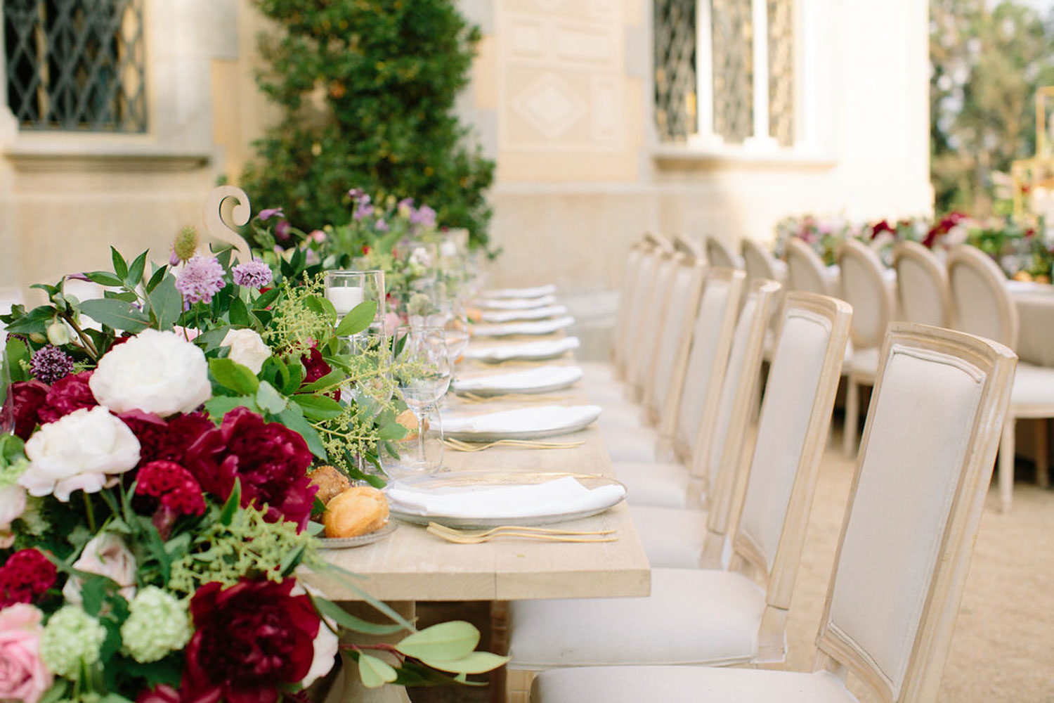 Table set up gold cutlery wood tables burgundy flowers Barcelona